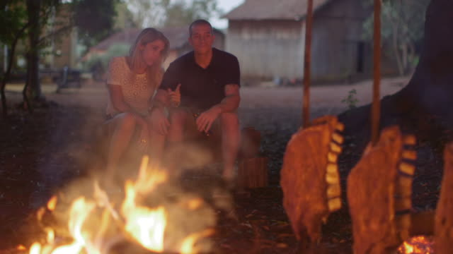 MS A couple sit talking and drinking at a barbecue / Maringa, Brazil
