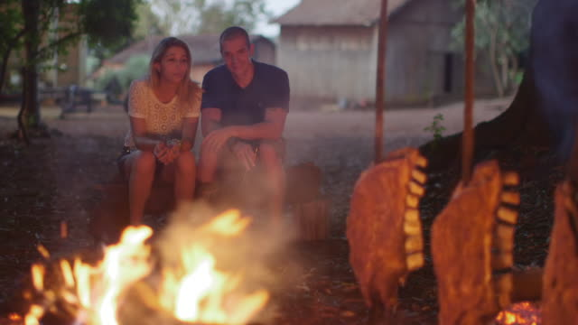 vídeos de stock, filmes e b-roll de ms a couple sit talking and drinking at a barbecue / maringa, brazil - vida simples