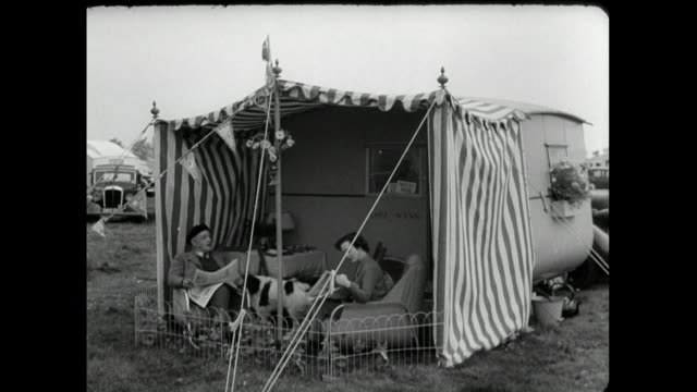 couple sit under striped awning with caravan and dog; 1950 - news not politics stock videos & royalty-free footage