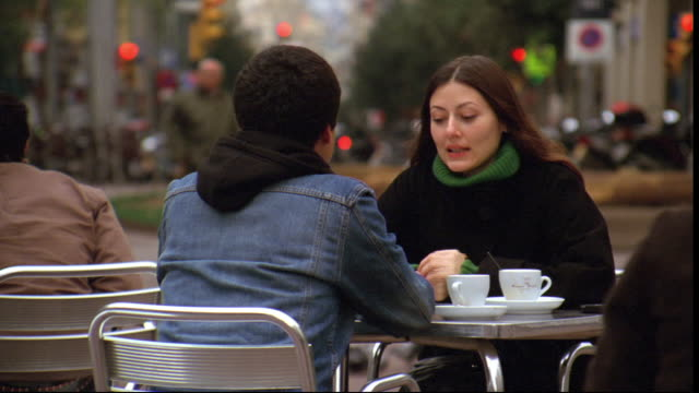 A couple sits and talks at an outdoor cafe.