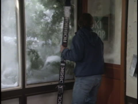 a couple sits and talks inside a ski shop. - ski pole stock videos & royalty-free footage