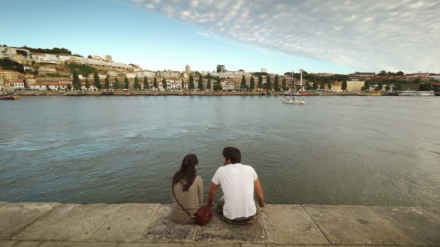 vídeos de stock e filmes b-roll de couple sits by douro river in porto, portugal in late afternoon - anoitecer