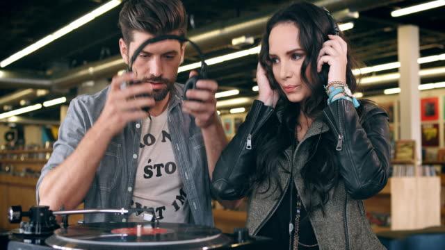 vídeos y material grabado en eventos de stock de a couple sits down to listen to a record while shopping in a recod store. - tienda de discos