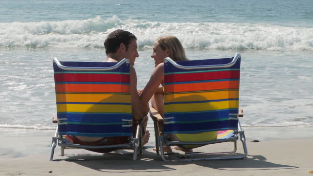 vídeos y material grabado en eventos de stock de couple sits in beach chairs at waters edge at the beach - bañador de hombre