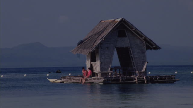 A couple sits on a boat floating alongside a wooden hut.