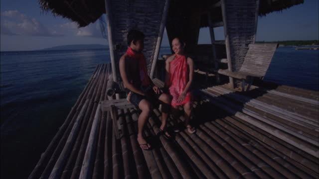 vidéos et rushes de a couple sits on a pier. - cahute