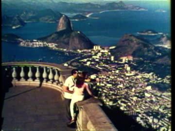 1953 ws pan couple sits on top of large cliff overlooking city / rio de janeiro, brazil / audio - rio de janeiro bildbanksvideor och videomaterial från bakom kulisserna