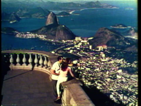 vídeos de stock, filmes e b-roll de 1953 ws pan couple sits on top of large cliff overlooking city / rio de janeiro, brazil / audio - 1950