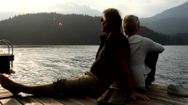 couple sitting admiring sunrise on dock - mature couple stock videos & royalty-free footage