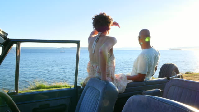 ms pan couple sitting and leaning on convertible parked along waterfront pointing and looking out at water - サンドレス点の映像素材/bロール