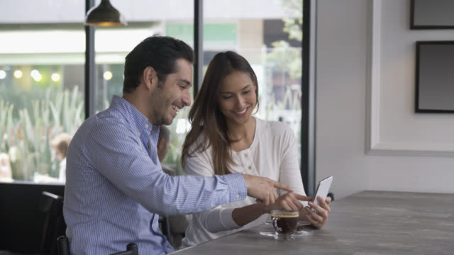 Couple sitting and looking at pictures on smartphone
