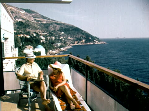 vídeos de stock e filmes b-roll de 1960 ms couple sitting and reclining on balcony and looking at view of the mediterranean sea - 1960