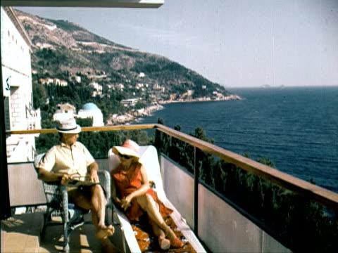 vídeos y material grabado en eventos de stock de 1960 ms couple sitting and reclining on balcony and looking at view of the mediterranean sea - 1960