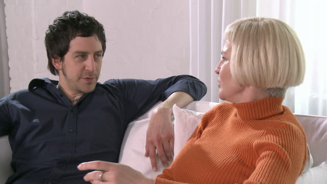 ms zi couple sitting and talking on couch/ cu man talking/ berlin, germany - polo neck stock videos & royalty-free footage