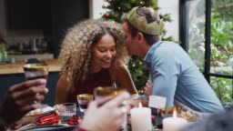 Couple Sitting Around Dining Table At Home For Christmas Dinner With Friends Talking And Whispering