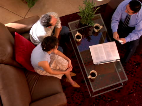 ha, zi, cu, couple sitting at coffee table listening to financial advisor - coffee table stock videos & royalty-free footage