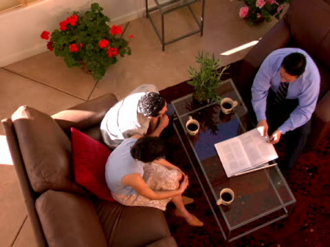ha, zi, cu couple sitting at coffee table listening to financial advisor - coffee table stock videos & royalty-free footage