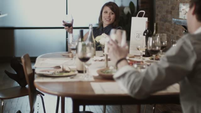 vídeos y material grabado en eventos de stock de slo mo ms couple sitting at dining table and toasting wine after party / new york city, new york, usa - cena con amigos