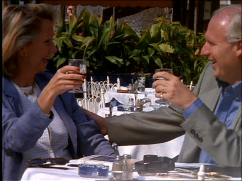 Couple sitting at outdoor table of cafe toasting wine