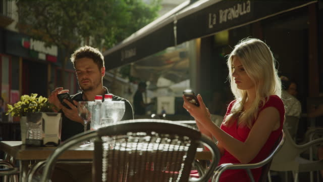 couple sitting at sidewalk cafe ignoring each other using cell phones / seville, sevilla, spain - distracted stock videos & royalty-free footage