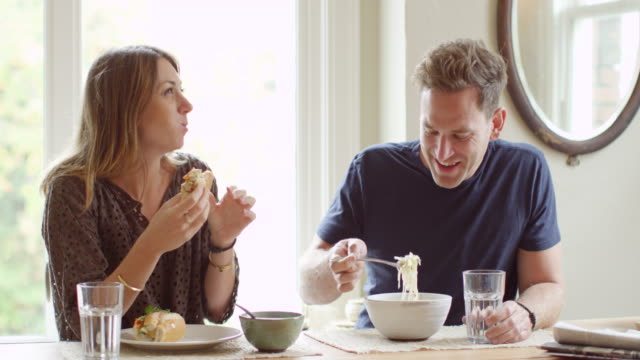 MS Couple sitting at table in home eating lunch together