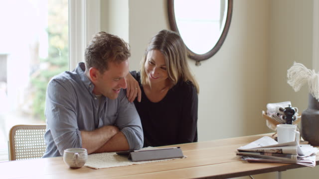 MS Couple sitting at table in home looking at digital tablet