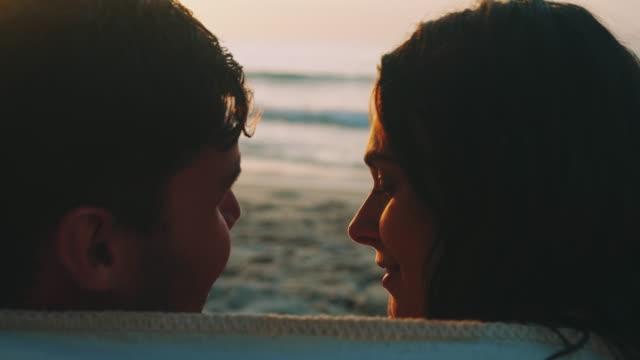 stockvideo's en b-roll-footage met paar zittend op het strand - leunen