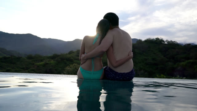 couple sitting at the edge of the pool embracing enjoying the sunset - semi dress stock videos & royalty-free footage