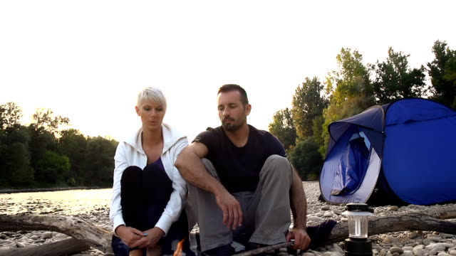 HD SUPER SLOW-MO: Couple Sitting By A Campfire