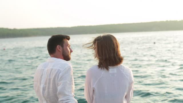 pan cu couple sitting by the sea being intimate. - ブラック島点の映像素材/bロール