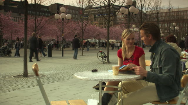a couple sitting in a caf? stockholm sweden. - pavement cafe stock videos and b-roll footage