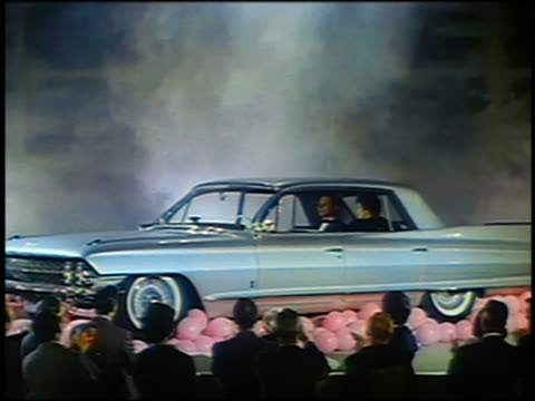 vídeos de stock, filmes e b-roll de 1961 couple sitting in cadillac at car show / audience in foreground / industrial - cadillac