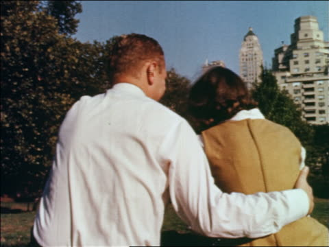 1960 rear view couple sitting in central park / man has arm around woman's shoulders / nyc - anno 1960 video stock e b–roll