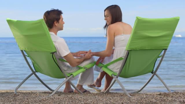 vídeos de stock, filmes e b-roll de hd: casal sentado em cadeiras de praia - cadeira dobrável