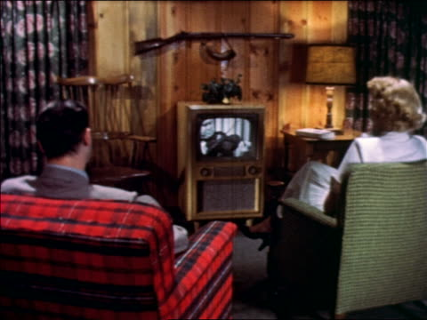 vidéos et rushes de 1952 rear view couple sitting in chairs watching violinist on television in living room - television show