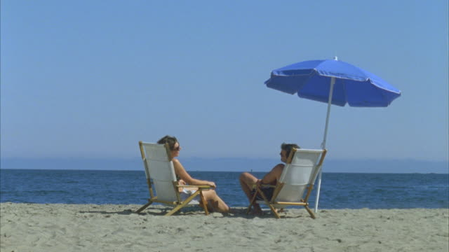WS Couple sitting in deck chairs on beach under umbrella then boy and girl run over / Phippsburg, Maine, USA
