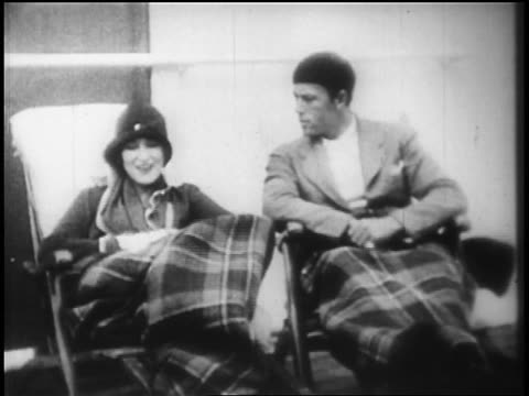 B/W 1928 couple sitting in deck chairs with blankets on ocean liner / newsreel