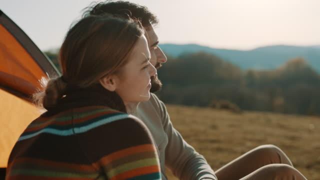vídeos y material grabado en eventos de stock de pareja sentada frente a la tienda y mirando en la distancia - pareja joven