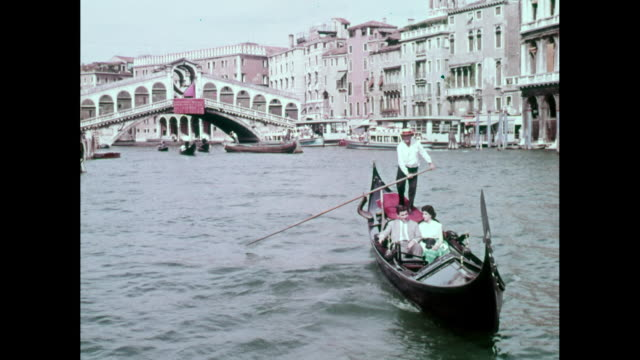 ws ts couple sitting in gondola on grand canal, rialto bridge behind them / venice, italy - grand canal venice stock videos & royalty-free footage