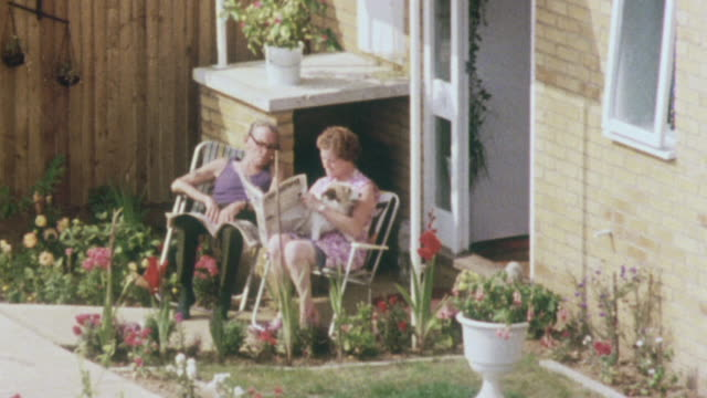 1980 zo couple sitting in lawn chairs surrounded by potted flowers under home's stoop reading newspaper and neighborhood terraced housing development / united kingdom - doppelhaus stock-videos und b-roll-filmmaterial