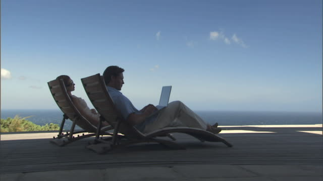 ws couple sitting in lounge chairs on deck overlooking the ocean, with man using laptop/ cape town, south africa - terrazza in legno video stock e b–roll