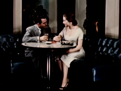 vidéos et rushes de 1956 ws couple sitting in round leather restaurant booth / usa - trinquer