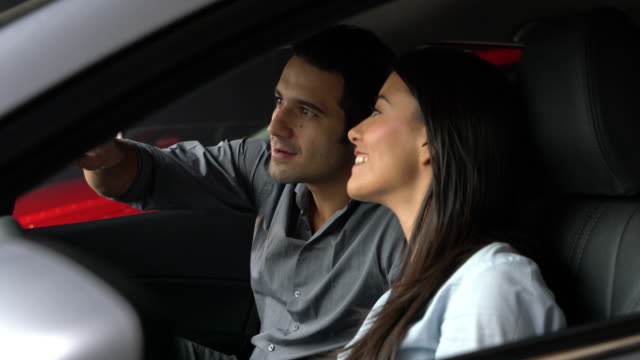 couple sitting in the interior of a car looking at all the commodities - test drive stock videos & royalty-free footage