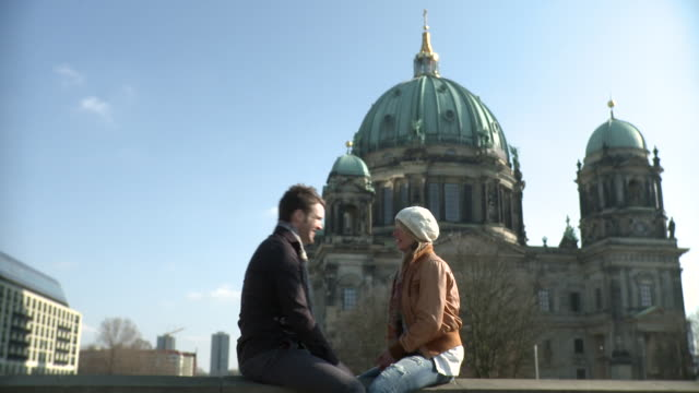 MS Couple sitting infront of Berlin cathedral / Berlin, Germany
