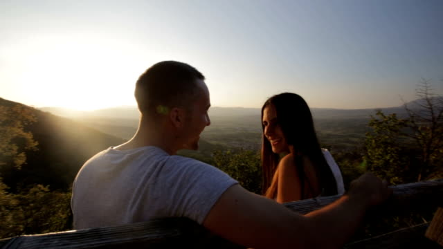 Couple sitting on a bench looking out to sunset