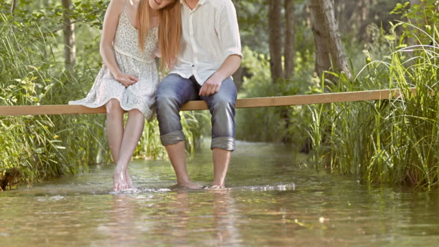 SLO MO Couple sitting on a footbridge with their feet in the brook