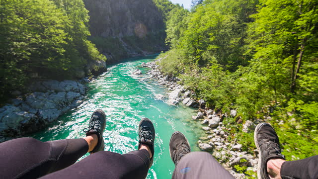 vídeos de stock e filmes b-roll de couple sitting on a hanging bridge, looking at mountain stream bellow, dangling with their feet - azul turquesa