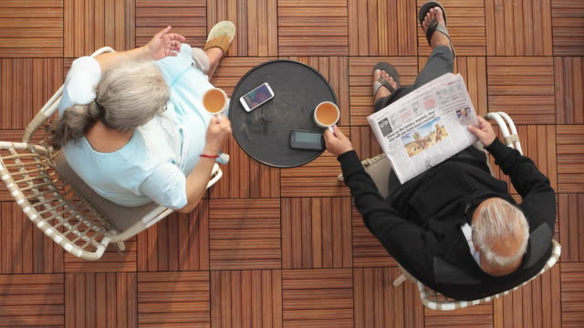 a couple sitting on a porch and sharing morning drink - paper stock videos & royalty-free footage