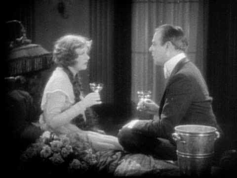 stockvideo's en b-roll-footage met ms, cu, b&w, couple sitting on bed, man getting woman drunk, 1920's  - actrice