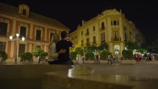 couple sitting on bench photographing plaza at night with cell phone / seville, sevilla, spain - städtischer platz stock-videos und b-roll-filmmaterial